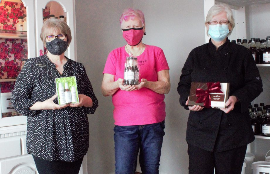 Three people wearing masks holding a gift basket.