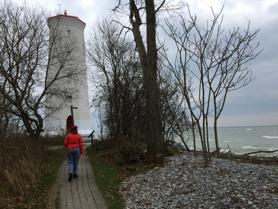 A person wearing a red sweater walking down a stone path towards a white lighthouse.