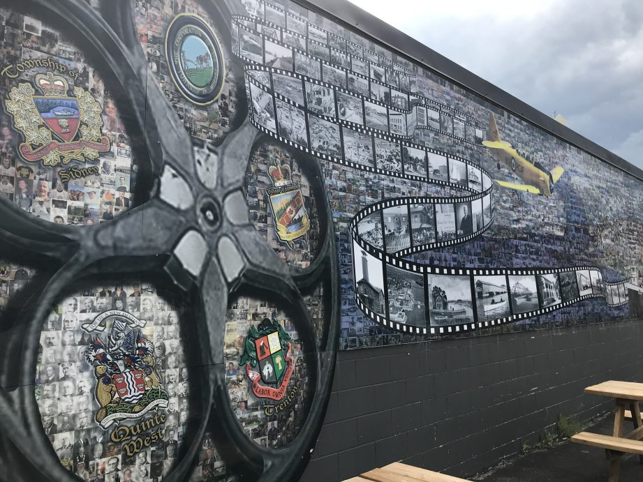 A long wall outdoors with a painted mural of a film reel and an airplane.
