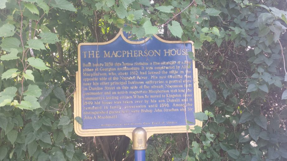 An historic blue sign outlining the history of the Macpherson House in Napanee.