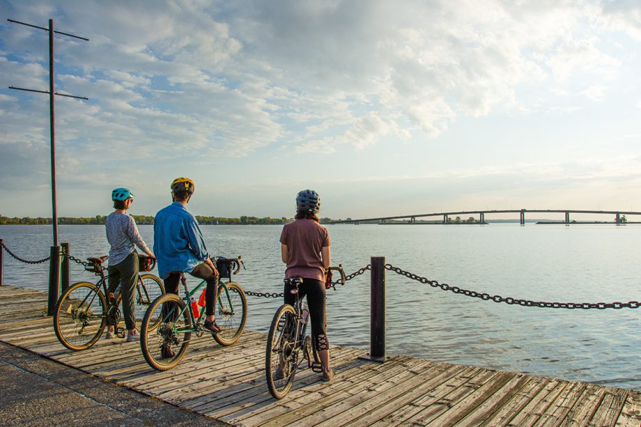 Three people on bicycles side-by-side on a boardwalk facing the water.