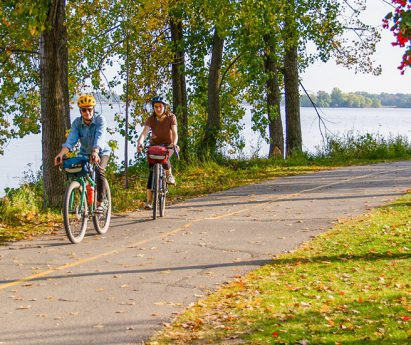 Three people cycling on a paved path next to grass and trees, with water in the background.