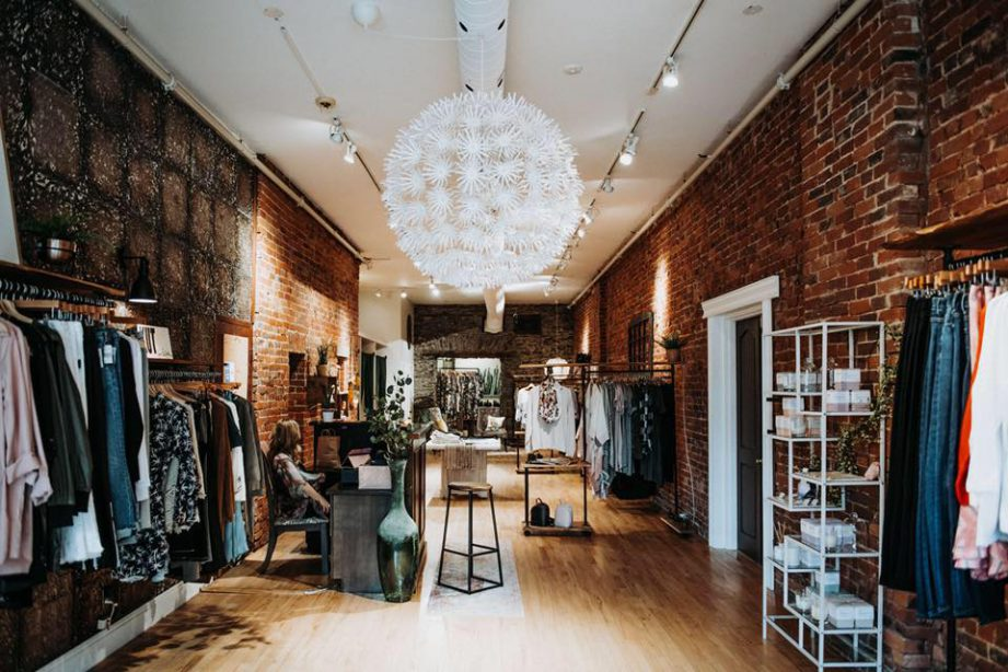 Interior of a clothing store with exposed brick walls and a large chandelier. Downtown Belleville.
