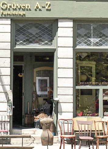 A storefront in downtown Belleville with refurbished and vintage furniture on display on the sidewalk.