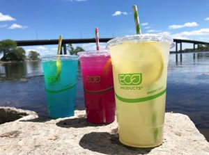 Three glasses of lemonade, yellow, pink and blue, lined up on a rock next to the Bay of Quinte. At the Pop-ups on the Bay in Zwick's Park.