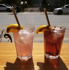 Two glasses of iced tea with straws and lemon wedges on a counter at Lola's Cafe in Brighton.