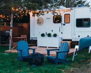 A modern RV with Adirondack chairs and a campfire, with string lights overhead.
