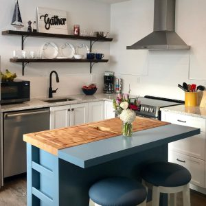 A kitchen at a room at the Spinnaker Suites in Brighton. A modern white kitchen with stainless steel appliances and a blue island in the centre.