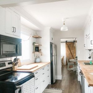 The kitchen at Strawberry Hallow Airbnb in Quinte West, Ontario. The room is white and bright with wooden counters.